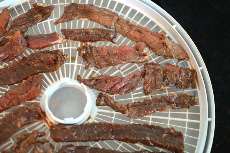 Sliced top round marinated in with a sweet and spicy marinade that is SO addicting. The jerky is perfect for a road trip or camping trip. from thatsquareplate.com