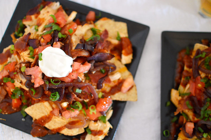 The homemade root beer barbecue sauce is what MAKES this dish! Warm BBQ chicken, cheese, caramelized onions and bacon top these sweet, semi-spicy nachos. Garnish with tomatoes, green onions, and sour cream if you want to max out the flavor! Recipe from thatquareplate.com